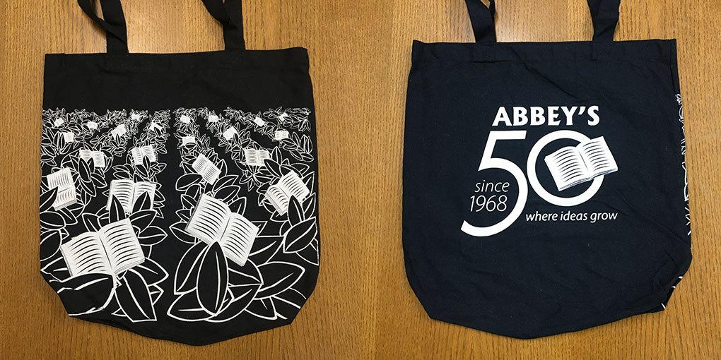 Photo of front and back of the tote bag. Entirely black cotton bag with white printed graphics on each side